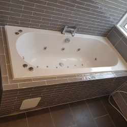 jacuzzi bath surrounded by grey wall tiles